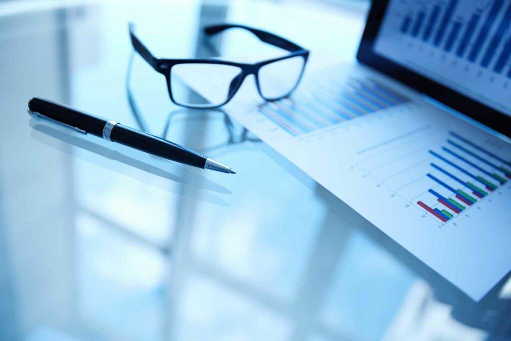 okulary i pióro na szklanym biurku